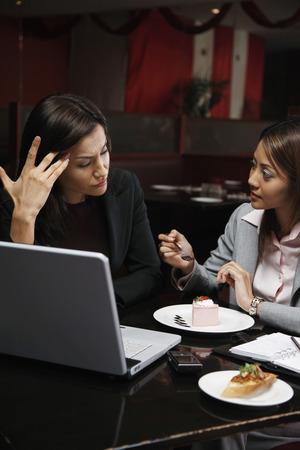 frowns: Businesswomen having discussion over dessert
