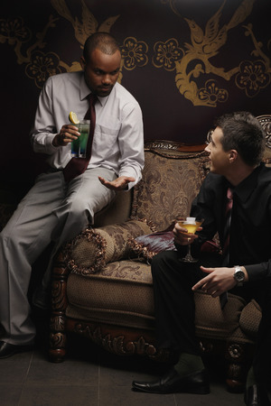 Businessmen sitting on antique sofa talking while having cocktails photo