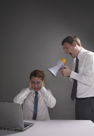 Businessman screaming through a megaphone, businesswoman covering her ears photo