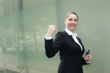 jubilate: Businesswoman holding cell phone, shaking fist in victory