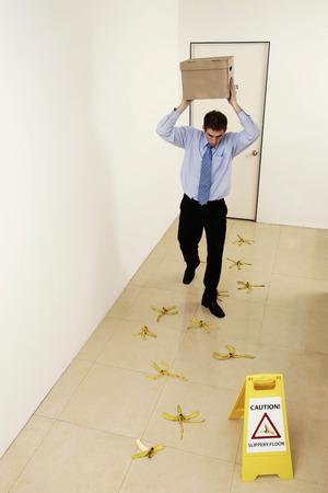 Businessman walking carefully on a slippery floor Stock Photo