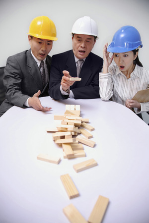 Business people playing wooden blocks game photo