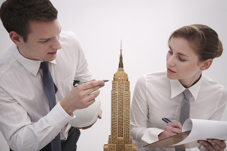 Business people examining model of Empire State Building photo