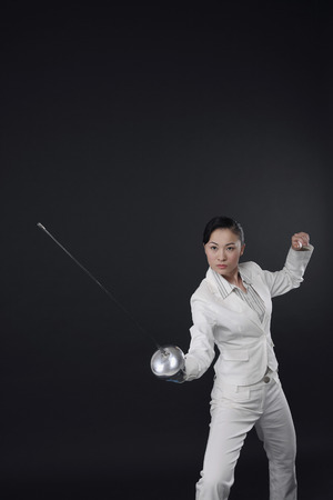 fencing foil: Businesswoman with a fencing foil Stock Photo