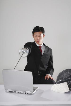 fencing foil: Businessman aiming at a laptop using a fencing foil