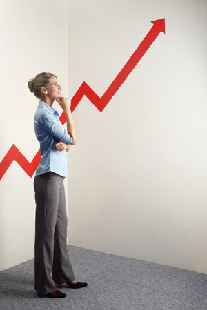 Businesswoman looking at a rocketing arrow sign Stock Photo - 26258865