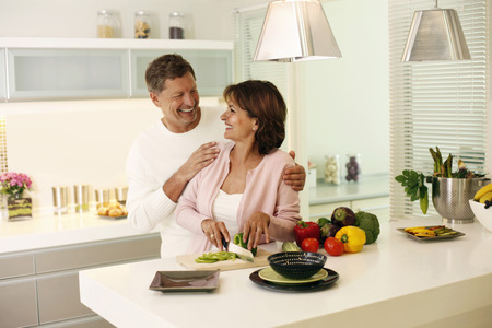 Woman smiling at man while cutting vegetable photo