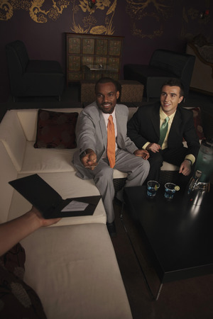 Businessman handing credit card to the waiter photo