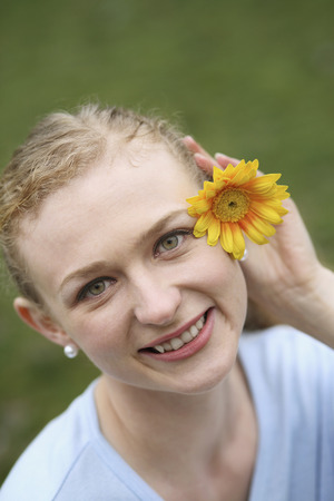 Woman decorating her hair with a sunflower photo