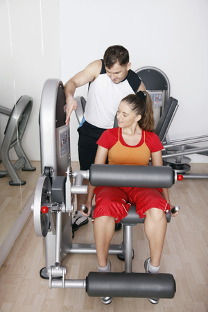 Woman exercising on gym equipment, personal trainer assisting her Stock Photo