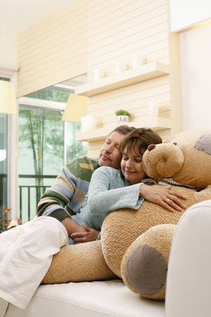 Man hugging woman, woman hugging teddy bear photo