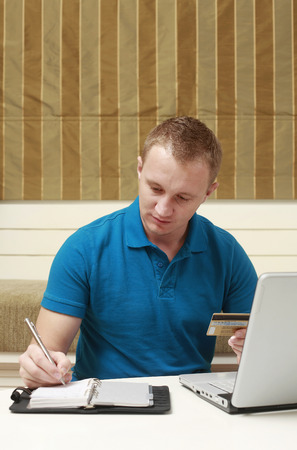 Man writing on organizer while holding credit card