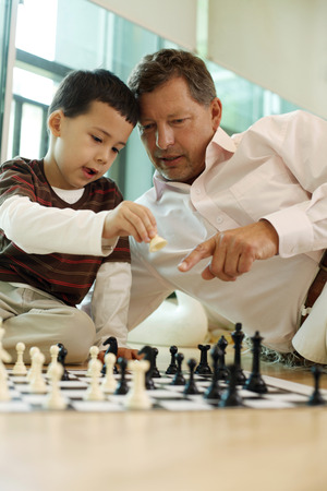 Man playing chess game with boy Stock Photo