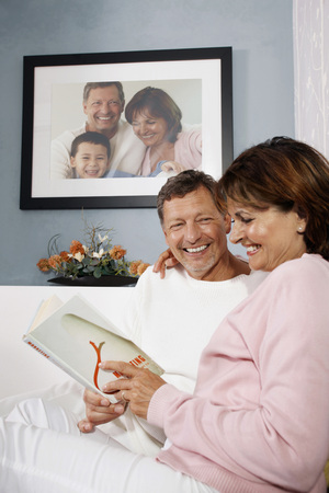 Man and woman reading book together Stock Photo