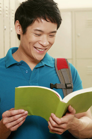 Man with backpack reading a book