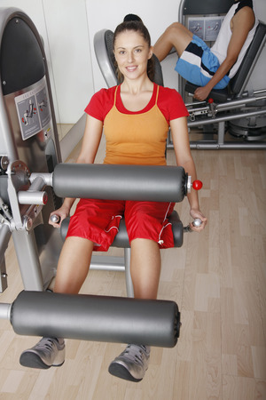 Woman exercising on gym equipment Stock Photo
