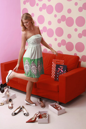 shoe boxes: Woman trying on different kinds of high heels Stock Photo