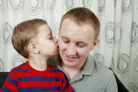 Boy giving man a kiss on the cheek