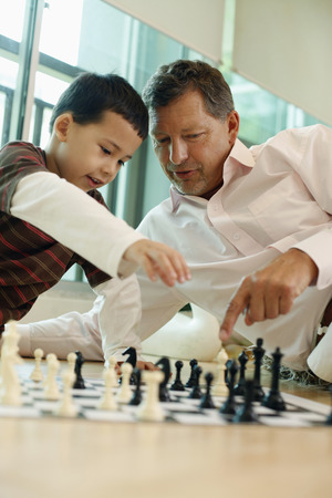 western european: Man playing chess game with boy Stock Photo