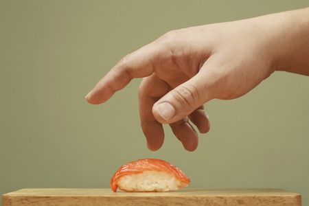 Man taking sushi from chopping board photo