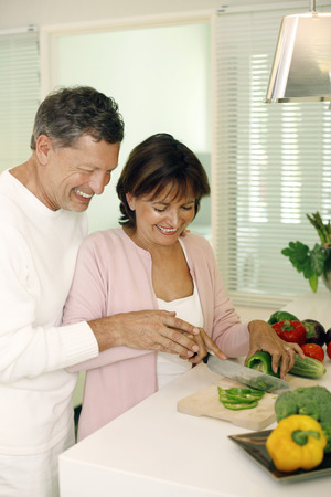 Man guiding woman in cutting vegetable photo