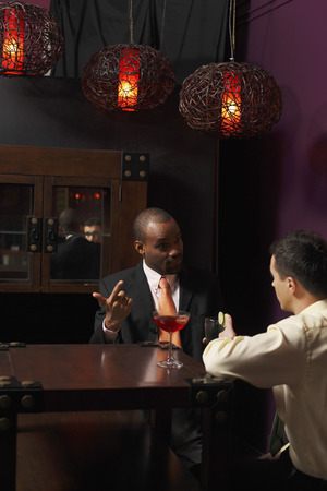 Businessmen having discussion over glasses of cocktails