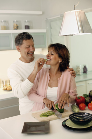 Woman cutting vegetable, man feeding woman photo
