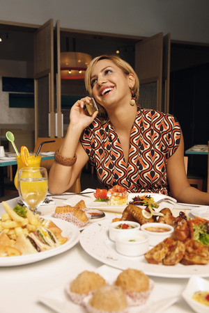 Woman talking on the mobile phone over lunch photo