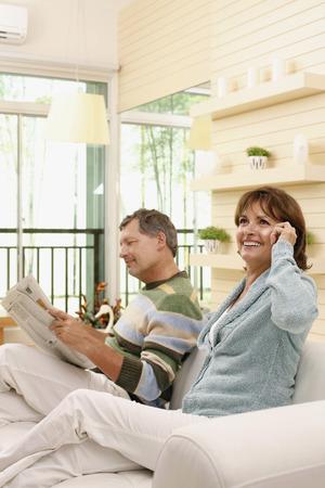 Man reading newspaper, woman talking on the phone photo