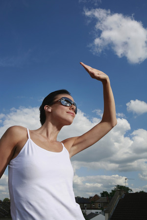 blocking: Woman wearing sunglasses, blocking the sunlight with her hand Stock Photo