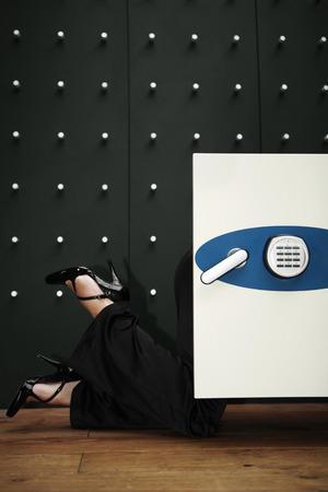 peering: Businesswoman peering into safe Stock Photo