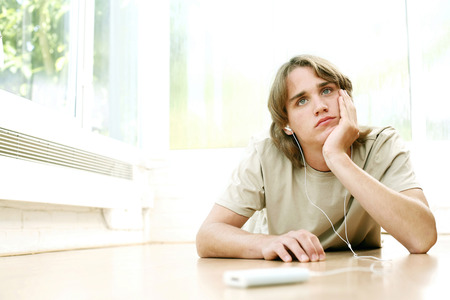 lying forward: Teenage boy lying forward on the floor listening to music on portable music player Stock Photo