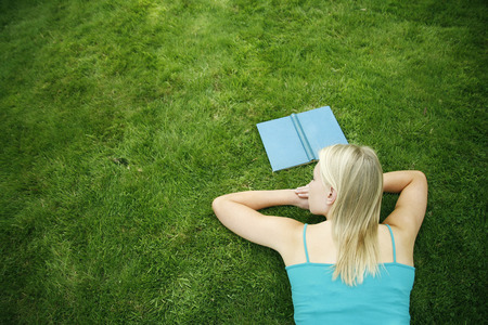 lying forward: Teenage girl lying forward on the field with book in front of her
