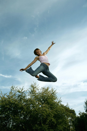 Teenage girl jumping with joy photo