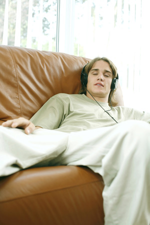 Teenage boy closing his eyes while listening to music on the headphones photo