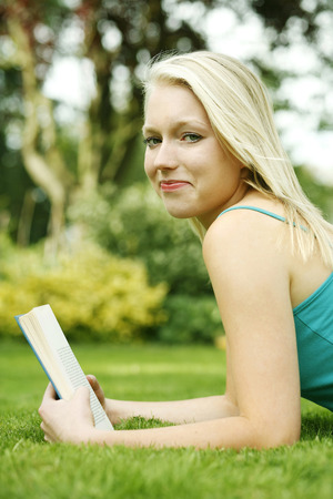 revision book: Teenage girl lying forward on the field holding book
