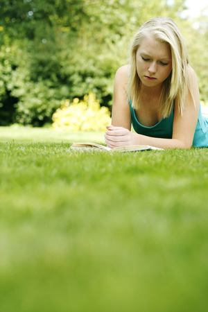 revision book: Teenage girl lying forward on the field reading book Stock Photo