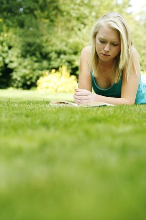 lying forward: Teenage girl lying forward on the field reading book Stock Photo