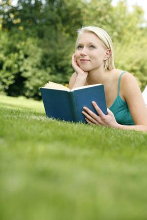 lying forward: Teenage girl lying forward on the field holding book