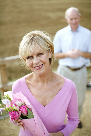 Senior woman holding a bouquet of flowers with her husband standing in the background photo