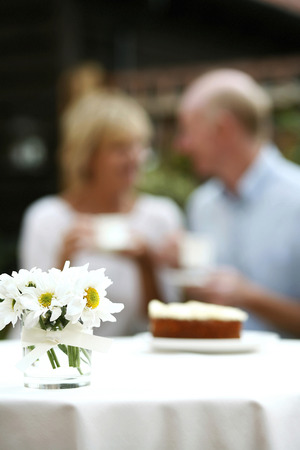 Focus on a vase of flowers with senior couple having tea in the background photo