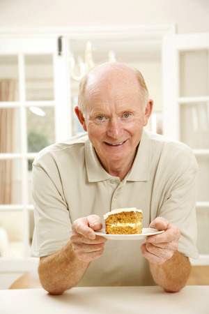 Senior man holding a plate of cake photo