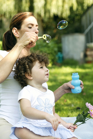 Mother and daughter playing with soap bubbles in the park photo
