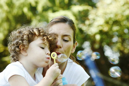 Mother and daughter blowing out soap bubbles together photo