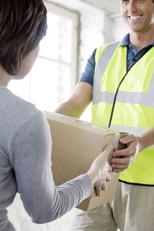 congeniality: A friendly delivery man passing over a parcel to customer Stock Photo