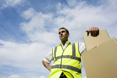 finished good: Low angle view of a delivery man beside some boxes