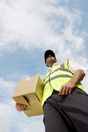 finished good: Low angle view of a delivery man carrying a box