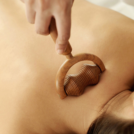 Hand using a wooden massager on womans back photo