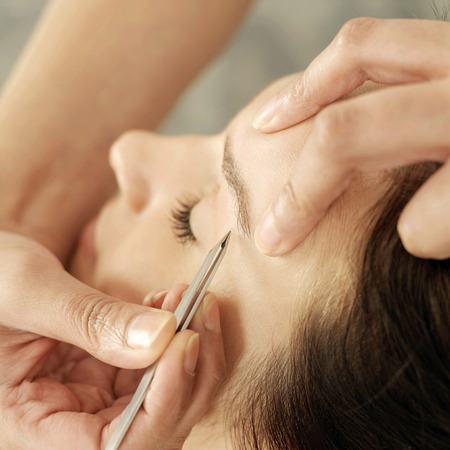 Hand tweezing womans eyebrow Stock Photo