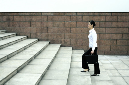 Businesswoman with briefcase walking up the stairs photo